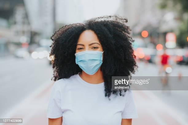 jovem na cidade sorrindo atrás da máscara de proteção facial coronavírus - só uma mulher jovem - fotografias e filmes do acervo