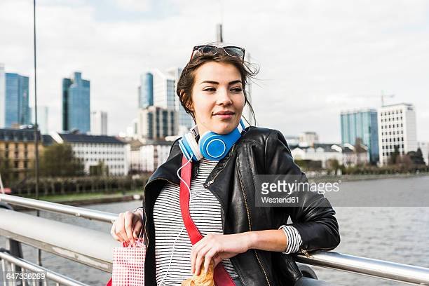 Young woman in the city with shopping bags and croissant