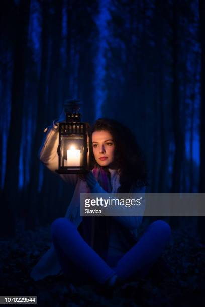young woman in the dark woods carrying the lantern - candle in the dark imagens e fotografias de stock