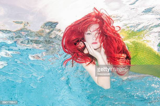 young woman in the disguise of arielle, the little mermaid, underwater - mermaid stock photos and pictures