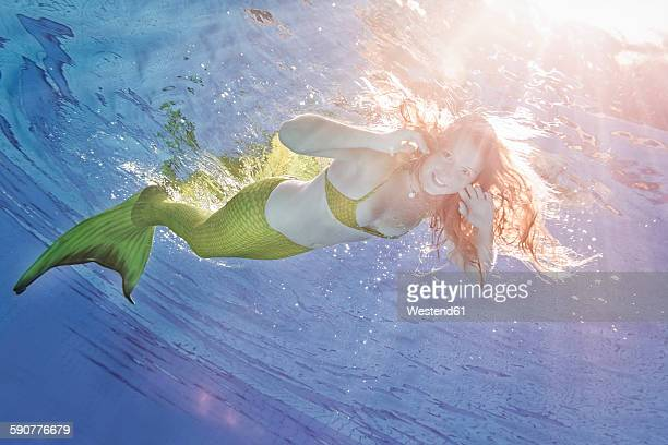 Young woman in the disguise of Arielle, the little mermaid, underwater