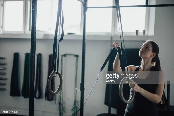 junge frau in der turnhalle bereitet sich zum training auf gymnastik ringen - frauen ringen stock-fotos und bilder