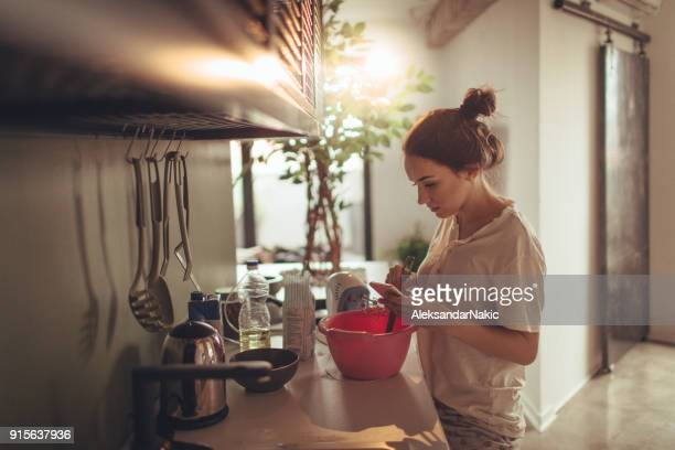 Young woman in the kitchen, reading recipe from the internet