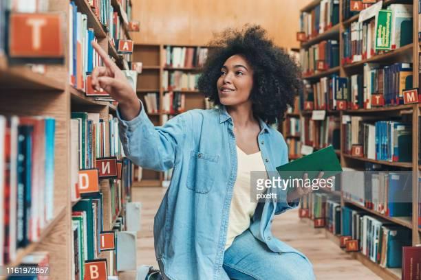 junge frau in der bibliothek - enzyklopädie stock-fotos und bilder