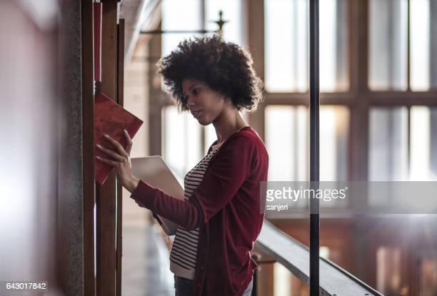 Jeune femme dans la bibliothèque se trouvant à côté de l'étagère et étudiant
