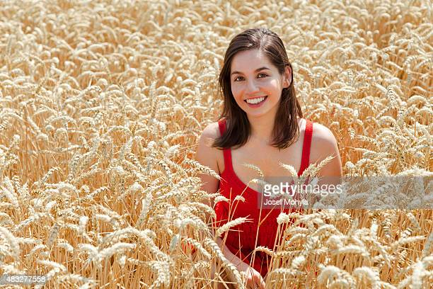 Young woman in the middle field of wheat