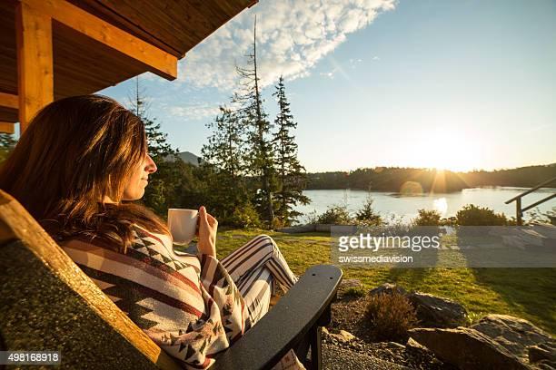 Mujer joven en la mañana Ver amanecer y bebiendo té