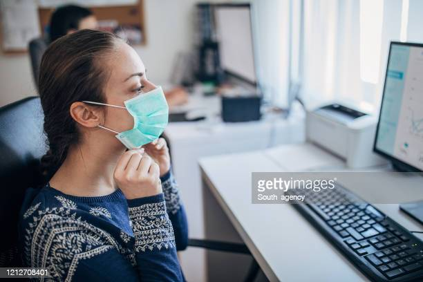young woman in the office putting on the protective mask, to prevent coronavirus from spreading - prevention imagens e fotografias de stock