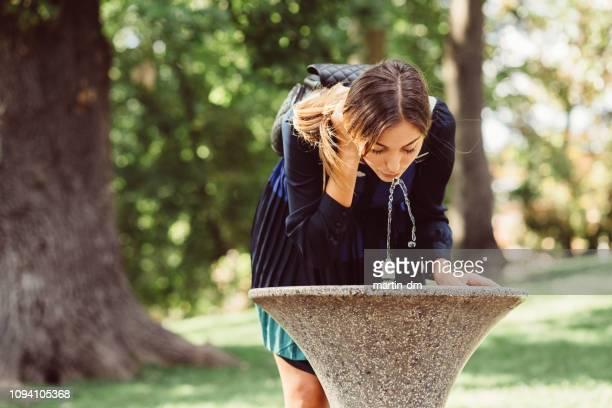 jeune femme dans le parc l'eau potable à une chaude journée d'été - eau potable photos et images de collection