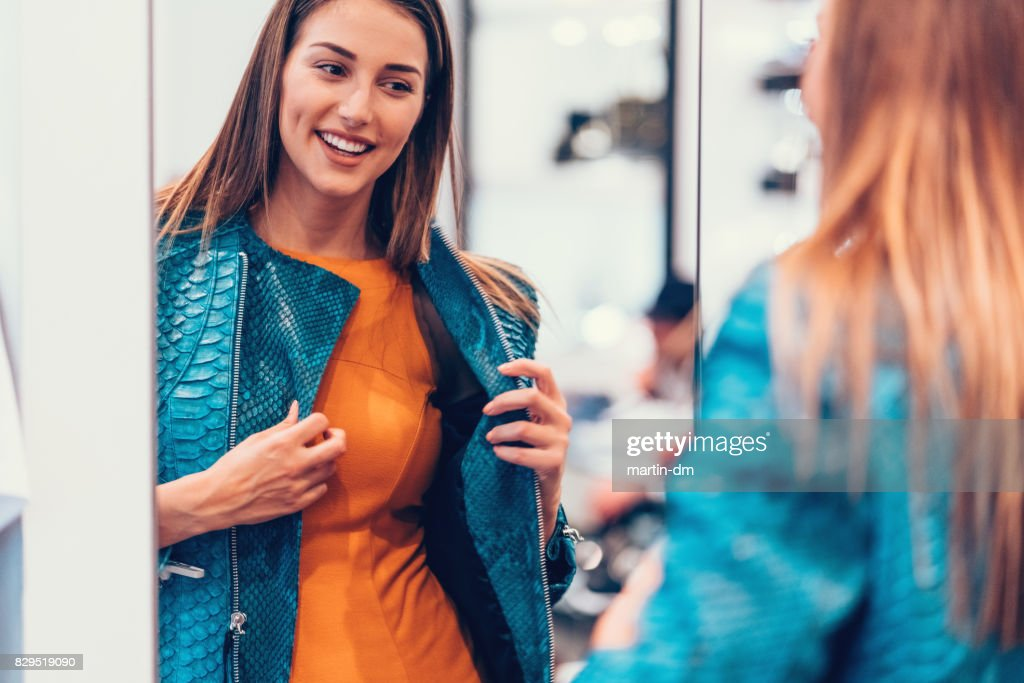 Young woman in the shopping mall enjoying a leather jacket : Stock Photo