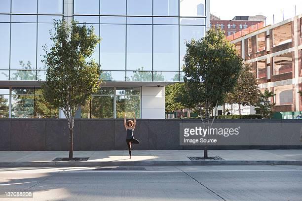 jovem mulher na rua fazendo yoga pose de árvore - calçada - fotografias e filmes do acervo