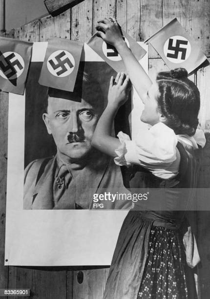 A young woman in the Sudetenland region of Czechoslovakia places swastika flags around a portrait of Nazi leader Adolf Hitler in anticipation of the...