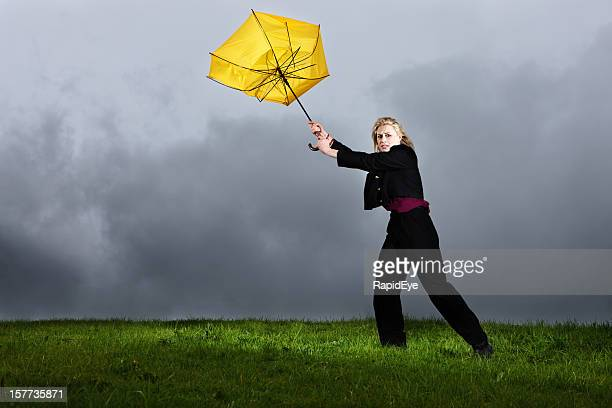 Young woman in thunderstorm about to lose her yellow umbrella