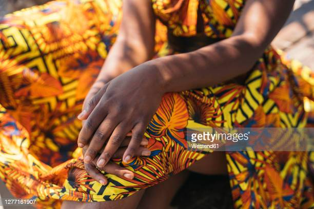 young woman in traditional clothing sitting on floor - multi colored dress stock pictures, royalty-free photos & images