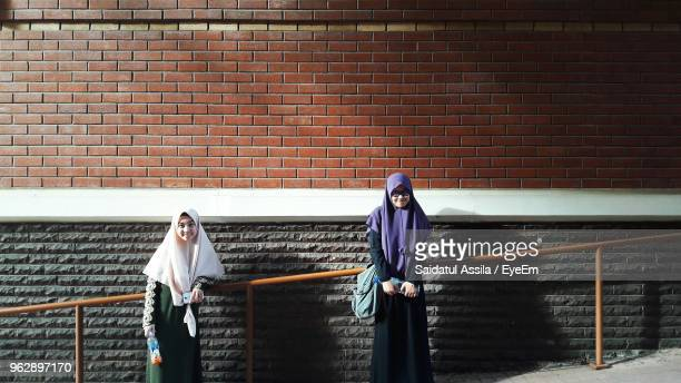 Young Woman In Traditional Clothing Standing Against Brick Wall
