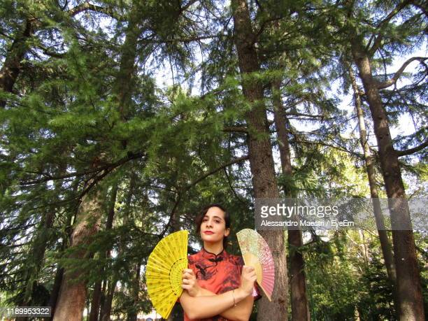young woman in traditional clothing standing against tree trunks - alessandro maestri foto e immagini stock