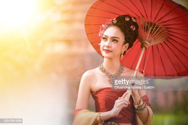 Young Woman In Traditional Clothing With Umbrella Standing Outdoors