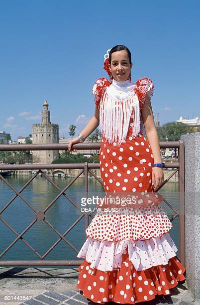 Young woman in traditional costume during the Feria de Abril with the Gold Tower in the background 12th century Seville Andalusia Spain