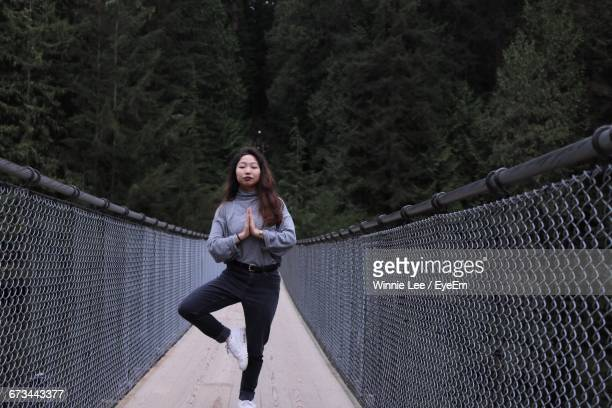 Young Woman In Tree Pose On Capilano Suspension Bridge Against Mountain