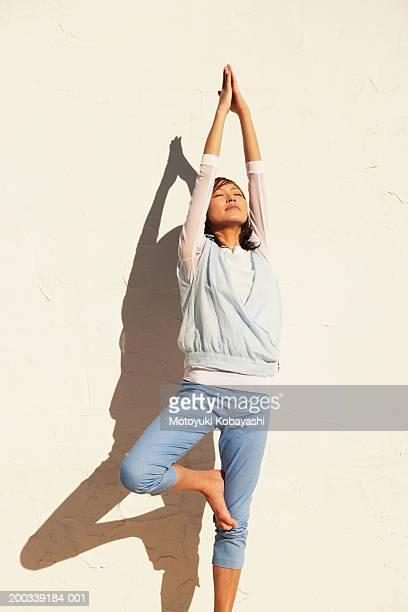 Young woman in tree pose