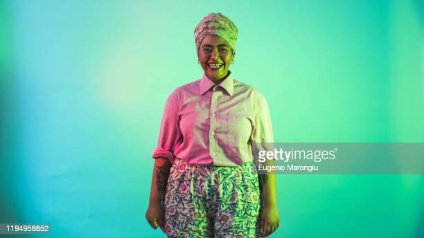 young woman in turban posing against turquoise background - sessão de foto - fotografias e filmes do acervo