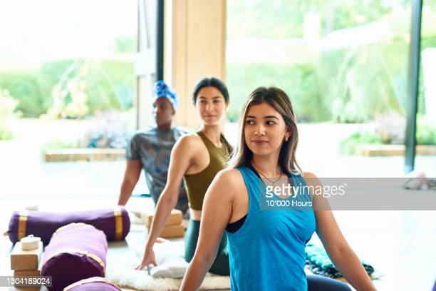 young woman in twisting pose in yoga studio - participant stock pictures, royalty-free photos & images