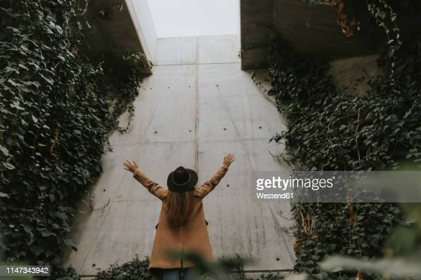 young woman in underground tunnel, concrete wall full of plants - creeper stock pictures, royalty-free photos & images