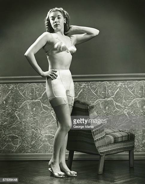Young woman in underwear and stockings posing indoors, (B&W)