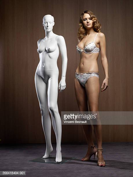 Young woman in underwear by mannequin, portrait