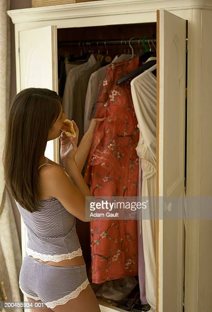 Young woman in underwear, choosing clothes from wardrobe