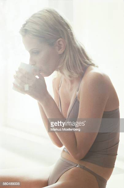 Young woman in underwear drinking a cup of coffee