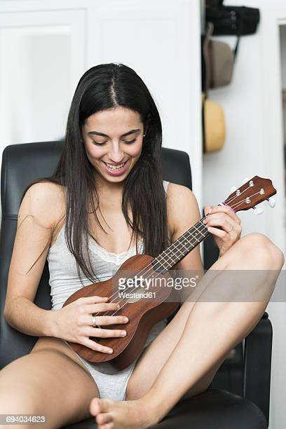 Young woman in underwear playing ukulele