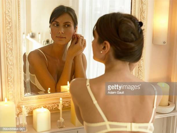 Young woman in underwear putting on earring in front of mirror