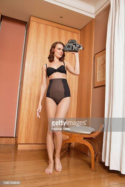 young woman in underwear using old-fashioned movie camera - see through knickers stock photos and pictures