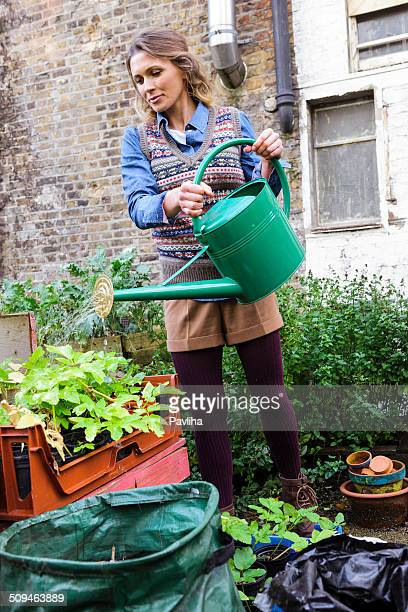 Young Woman In Urban City Garden Watering Plants, London, UK