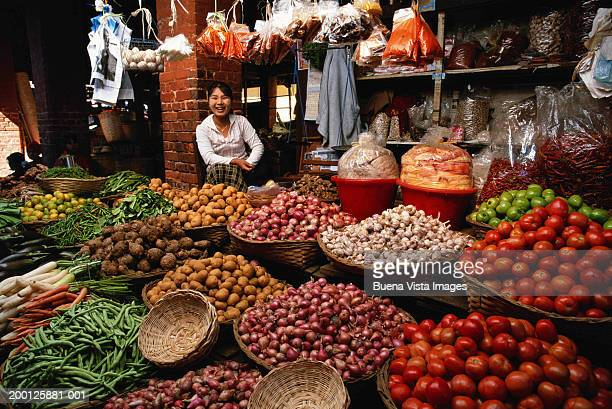 Young woman in vegetable market smiling, portrait