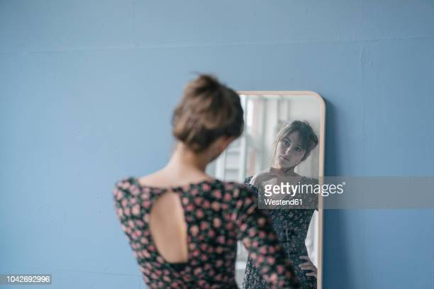 young woman in vintage dress looking into mirror - frauen stock-fotos und bilder