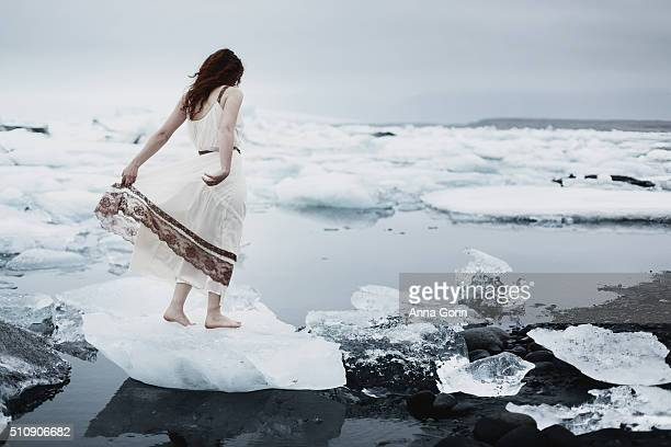 Young woman in vintage sheer white nightgown standing barefoot on iceberg at Jokulsarlon glacial lagoon, Iceland, back view
