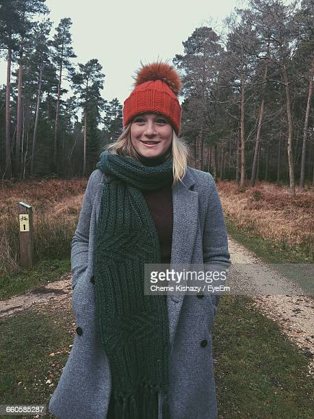 Young Woman In Warm Clothing Standing On Field