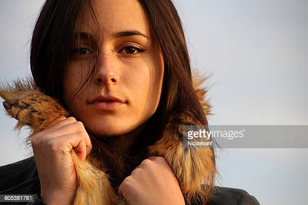 Young woman in warm coat with fur hood