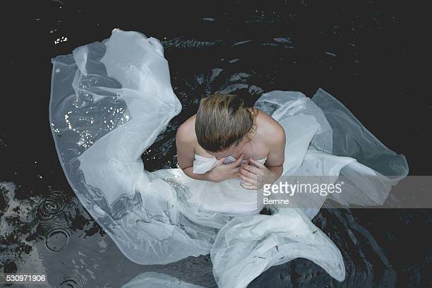 Young Woman in Water Wrapped in Long Sheer Fabric