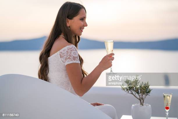 young woman in wedding dress with glass of sparkling wine