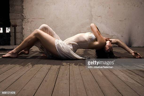 Young woman in wet dress lying on wooden floor