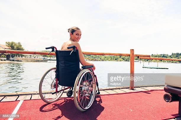 Junge Frau im Rollstuhl mit Meerblick