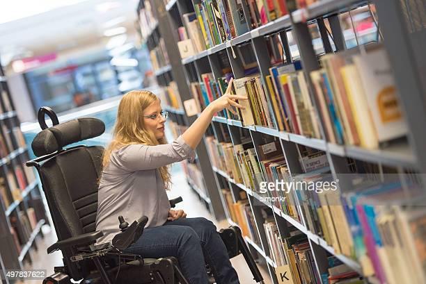 Junge Frau im Rollstuhl in der Bibliothek