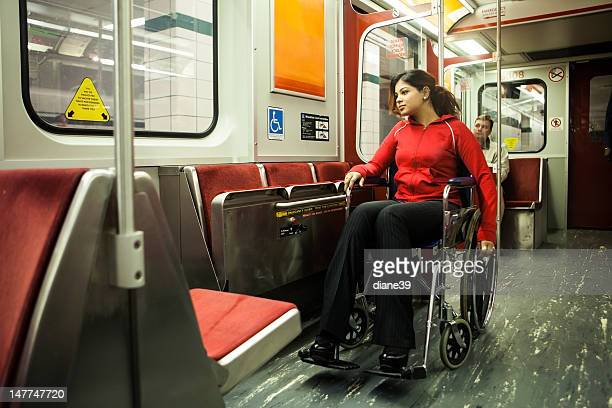 Young woman in wheelchair on a subway train