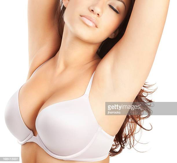 Young woman in white bra with raised arms