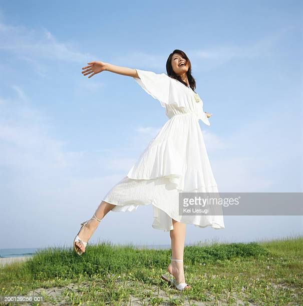 Young woman in white dress, dancing on beach