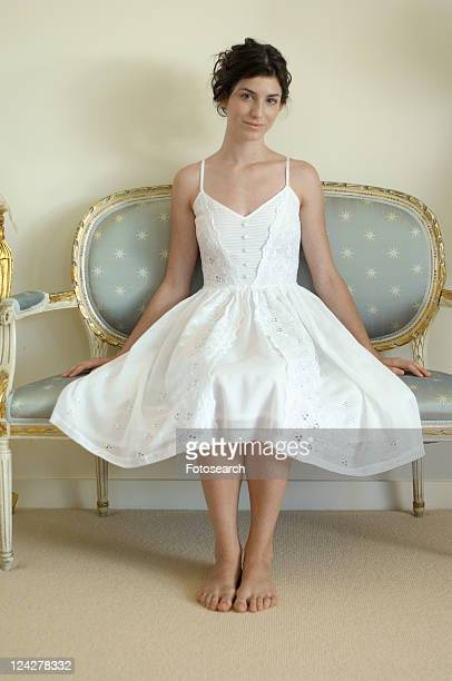 Young woman in white dress sitting on chair (portrait)