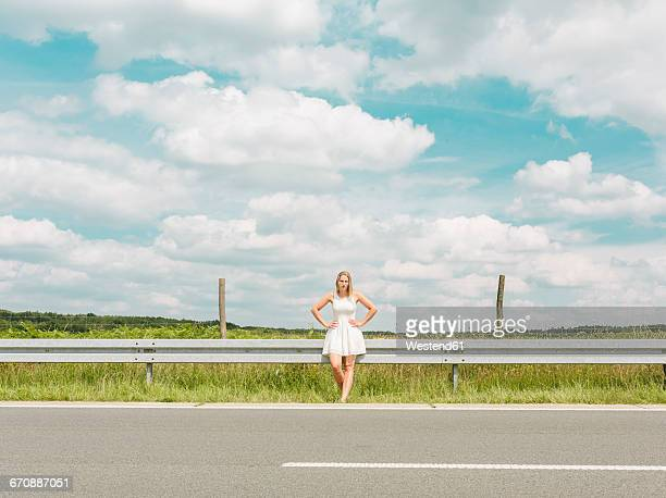 young woman in white dress standing at the roadside - leitplanke stock-fotos und bilder